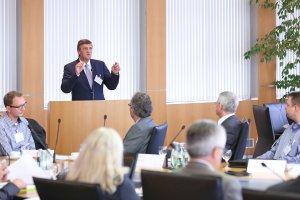 Martin Berg, Vorstandsvorsitzender der BAG WfbM, steht hinter einem Sprecherpult und spricht zum Publikum